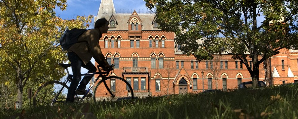 Student biking past Sage Hall