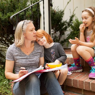 A graduate student sits on her front porch with her two young daughters.