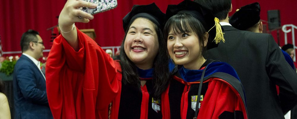 Two students at the doctoral hooding ceremony