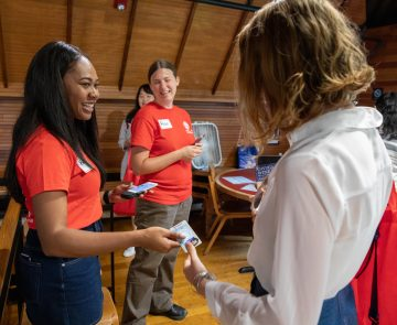 Volunteers hand incoming students IDs at Orientation.