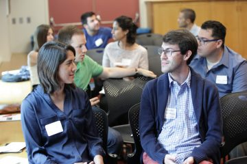 Amnon Ortoll-Bloch and a colleague engage in discussion at the Summer Success Symposium