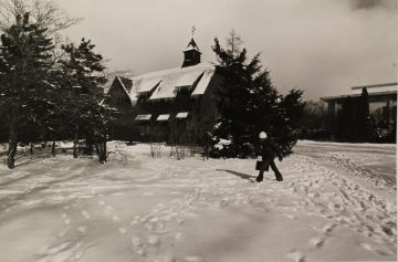 Student walking through snow outside historical Big Red Barn