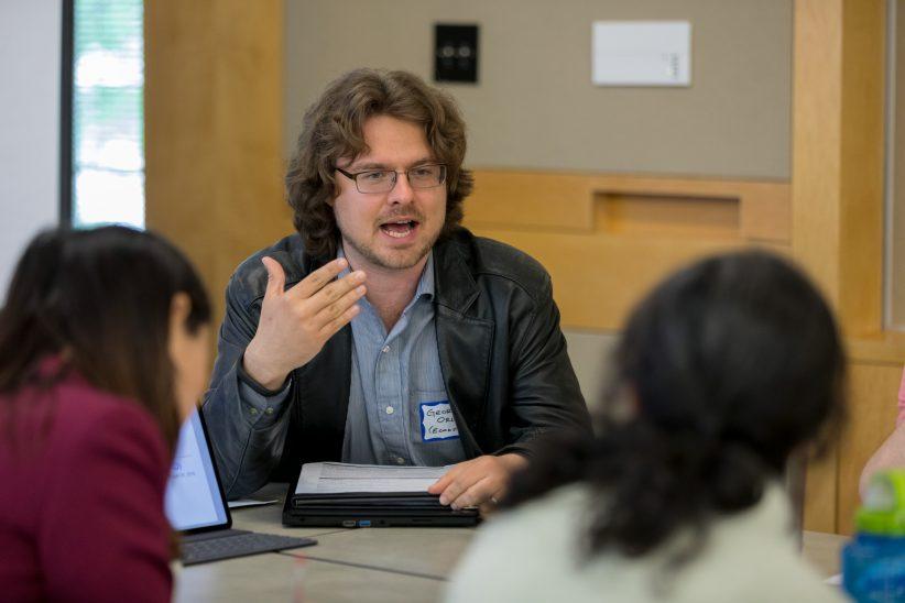 Economics postdoc George Orlov talks to colleagues