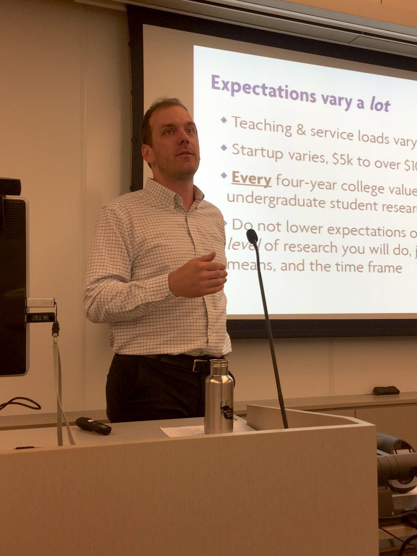 "Jeffrey Werner in front of a slide that reads ""Expectations vary a lot. Teaching and service load varies. Startup varies. Every four-year college values undergraduate research."""