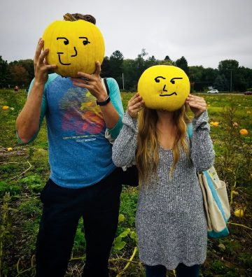 Students holding smiley face pumpkins in front of faces