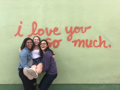 "Three students against mural saying, ""I love you so much"""