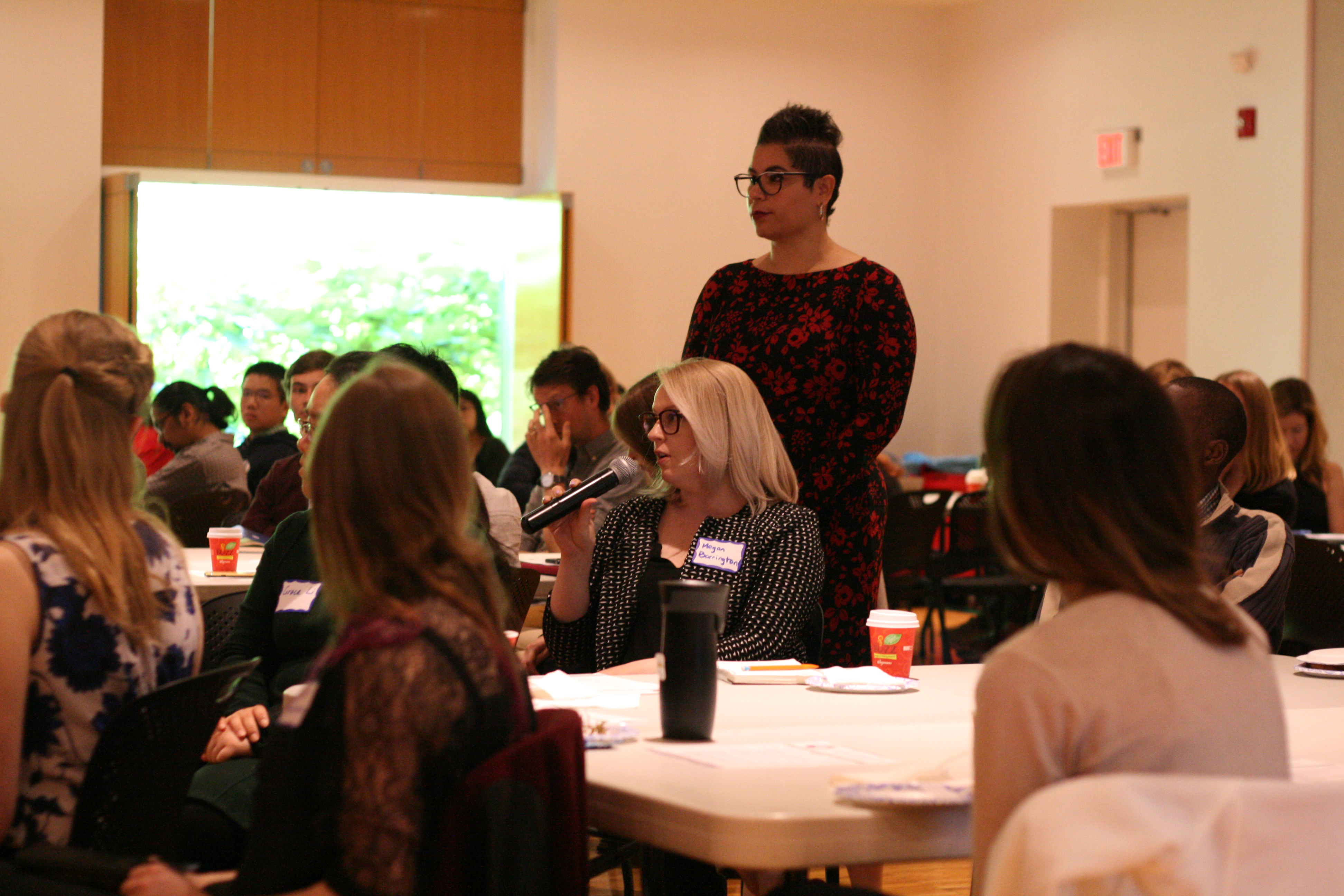 Sara Xayarath Hernández stands over a graduate student asking a question at a workshop