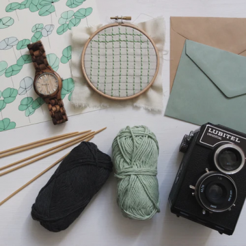 A watch, cross stitch piece, envelopes, yarn and knitting needles, and a camera on a table.