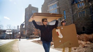 Students carrying cardboard boxes in Collegetown