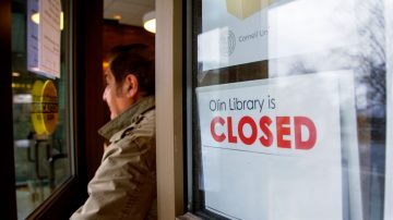 Man exiting Olin Library next to closed sign