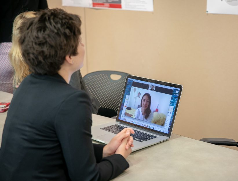 Alumna Emily Riddle speaks to a remote presenter on a laptop as she looks at the student's poster