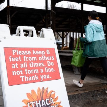 Person walking into the Ithaca Farmers Market next to a sign with instructions on social distancing