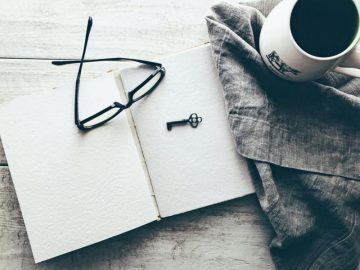 Glasses on blank notebook pages next to a cup of coffee