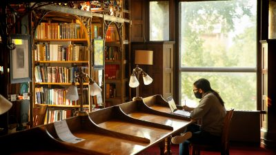 A student wearing a face mask and studying in the library