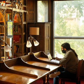 Student in a mask working in a library