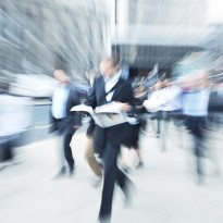 Blurred image of man holding a newspaper walking through a crowd