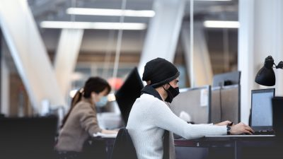 Two students, wearing masks, work on computers