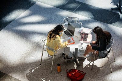 Two students wearing masks work at a table indoors