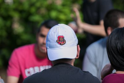 Student sits outside the Big Red Barn wearing a Cornell hat