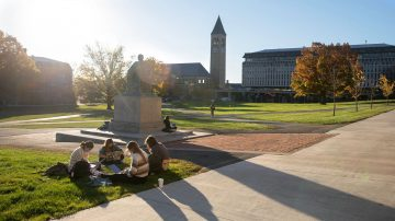 A group of students works together on the Arts Quad with McGraw Tower in the background