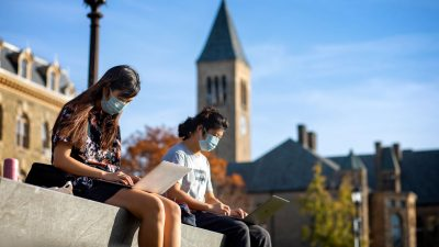Two students wearing masks work on laptops with McGraw Tower in the background