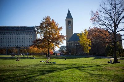 Students are spread across the grassy quad with McGraw Tower and the library in the background